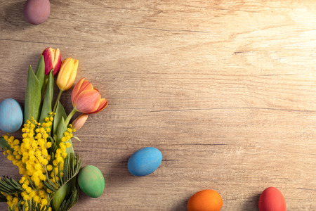 Easter eggs with tulips on wooden board, Easter holiday concept. Copy space for text. Фото со стока