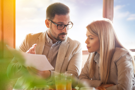 Man and woman meeting over coffee in a restaurant, discussing about project