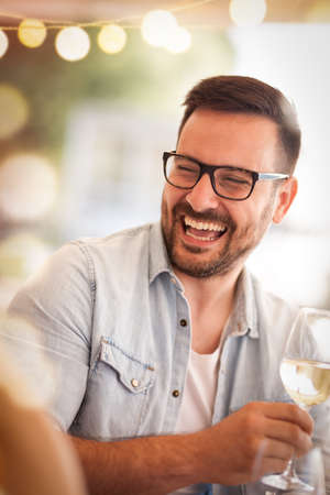 Portrait of young happy man on  party with wine glass in hand