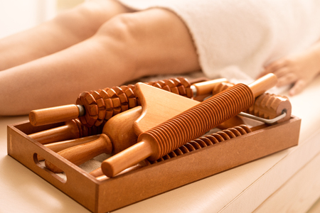 Female on  the massage table next to her is wooden massage tools for Maderotherapy.