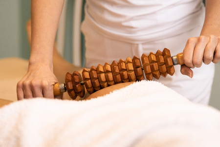 Close up of Madero therapy massage with wooden rolling pin