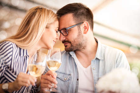 Young couple in love toasting with wine, tender moment Archivio Fotografico