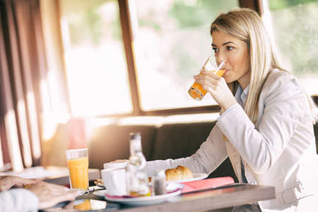 Beautiful businesswoman drinking orange juice and cheerful  listening her business colleague in coffee bar