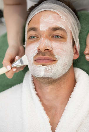 young man receiving skincare cosmetic treatment at spa salon