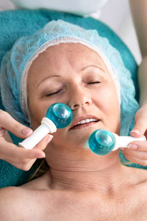 Woman in beauty salon during treatment facial massage with a cold glass balls Archivio Fotografico