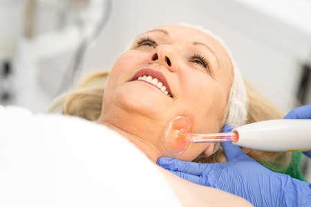 Beautiful senior, gray hair, woman getting a facial treatment. Concept of skincare, cosmetics, beauty salon, facial treatment, facial massage, wellbeing