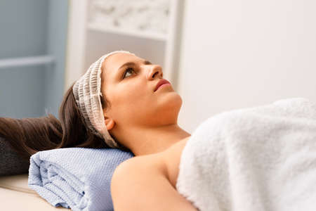 Healthy young woman lying on massage bed in spa salon Foto de archivo