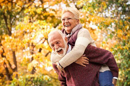 Älteres Paar, das im Herbstpark lacht und Spaß hat. Nach all den Jahren wie beim ersten Treffen