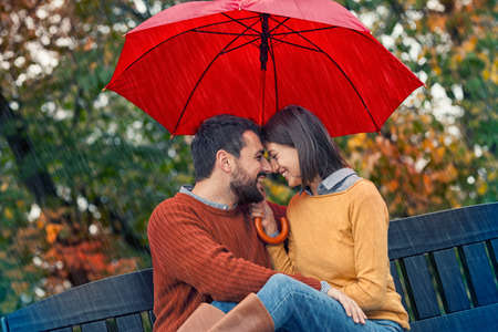 Smiling couple on rain. Autumn  rain with your lover... One of the most romantic moments ever.