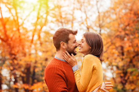 Nice loving couple in the autumn park- love, relationships, season and people concept