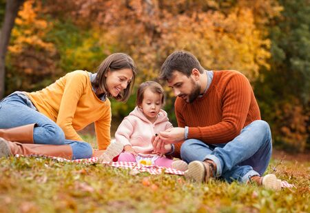 Family enjoying life together outside. Little girl with amazingly look on picnic. She meets with nature