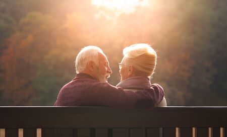 Senior couple sitting on bench in autumn park and looking sunset Banque d'images