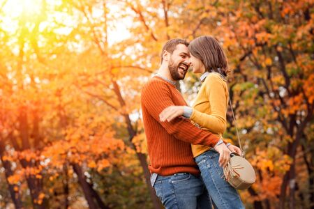 Young couple in love outdoor in autumn park. Couple hugging. Young beautiful couple in love staying and kissing on the autumn park on sunset. Soft sunny colors