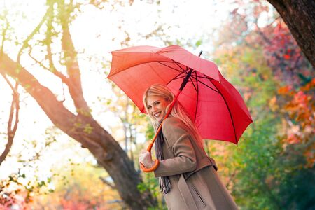 Young woman with red umbrella walking on autumn city park. Beautiful fall time in nature Imagens