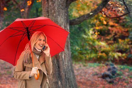 Woman using phone under umbrella on autumn walk through the city park Фото со стока