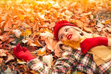 Season and people concept - beautiful young woman with autumn maple leaves lying on ground