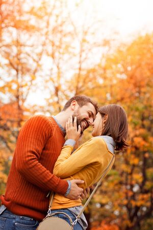 Happy and in love. Young cute couple in love staying and kissing on the autumn park on sunset Фото со стока