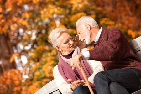 Happy elderly man and woman sitting on a bench with walking stick on autumn day. Relaxed senior couple sitting on a park bench Фото со стока