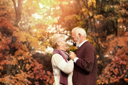 Romantic senior couple smiling and dancing on a autumn sunny day Standard-Bild - 131178872