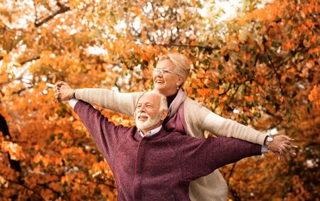 Happy loving couple. Happy senior man piggybacking his wife while keeping arms outstretched Stockfoto