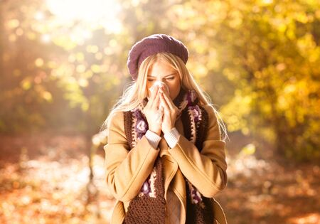 Woman coughing and blowing her nose in autumn. Cold and flu Stock Photo