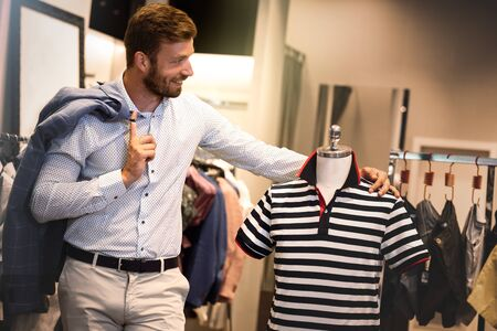 Smiling man in menswear store. I like this t-shirt