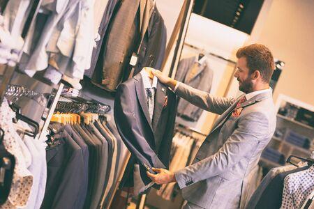 Hombre elegante joven que sostiene la chaqueta gris en la percha, mirando, eligiendo
