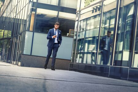 Young urban businessman professional on smartphone walking in street using app texting sms message on smartphone Standard-Bild - 131475598