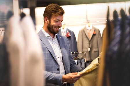 Handsome man in in men's cloths store, holds his pants in his hands and looks at them with a smile
