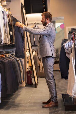 Man reaching for suit on hanger in menswear shop