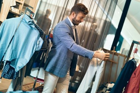 Trendy man in menswear store choosing pantaloons. Hes going through some pantaloons and choosing what would fit him the best.