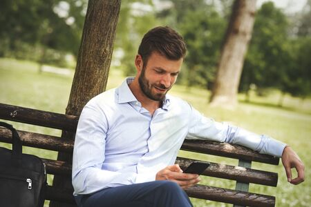 Happy casual business man outdoors texting on his phone and sitting on a bench at the park