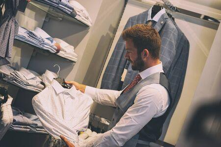 Young man choosing elegant white shirt during apparel shopping at clothing store
