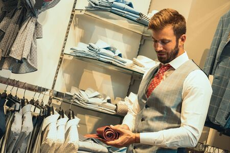 Smiling handsome man choosing some ties at retail store, he looks at his tie and wonders if will fit well with the suit