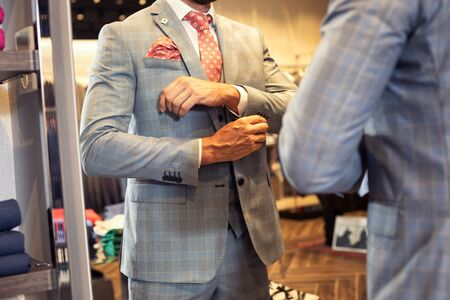 Handsome man in elegant suit standing, looking at mirror in boutique and choosing clothing. Young client in fashionable jacket, white shirt and red necktie. 版權商用圖片