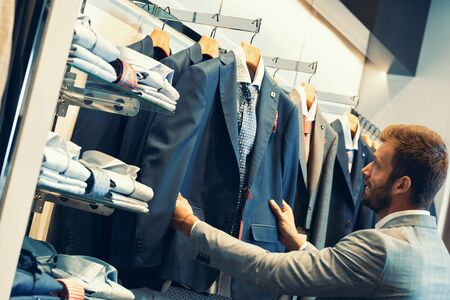 Elegant businessman choosing his new suit from new collection in clothing store Stockfoto
