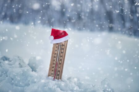 Wooden thermometer in Santa hat with Christmas temperature, ebullient Christmas