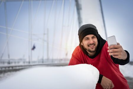 Satisfied sporty man take selfie to make note of beautiful  winter sporty day to share on social networks with friends