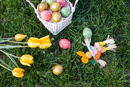 Top view of ester eggs  on grass with Easter decorations