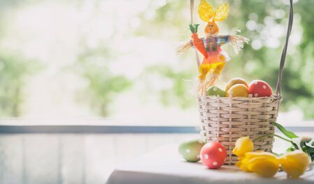 Basket of decorated eggs with yellow tulips next window- Easter holiday background