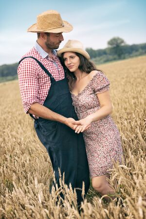 Love couple in wheat field, romantic couple in calm hug