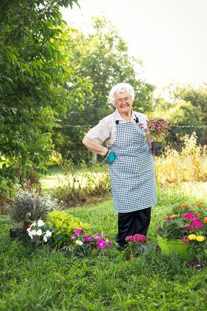 Happy woman gardener plant flowers. Woman care and grow flowers in garden. Gardener is happy for results. Banque d'images