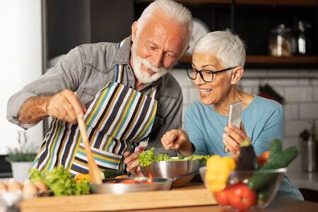 Modern and harmonious couple prepares their favorite recipe and shares with their friends via video call, fun and domestic life of pensioner