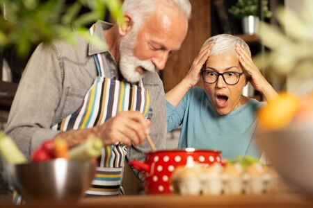 senior woman shocked, with open mouth looking at her husband's culinary masterpiece