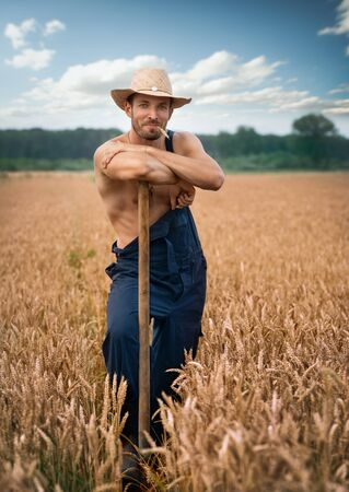 Sexy farmer with straw hat standing in wheat field leaning shovel