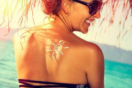 Beauty cheerful woman applying sun tan cream, enjoys the sun with UV protection