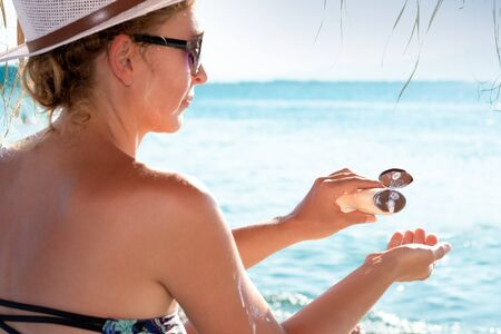 Beauty woman applying sunscreen cream on tanned skin. Skincare. Body Sun protection sun cream.