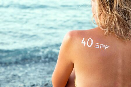 Woman with sunscreen in form of SPF 40 word on her back sunbathing at the beach. Sun protection factor concept.