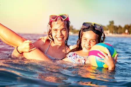 Cute two little girls having fun in blue sea water