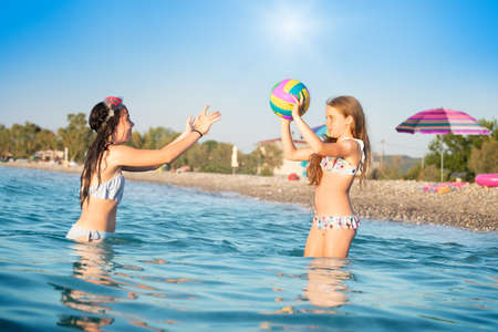 Two young girls/sisters playing with ball in water on summer vacation